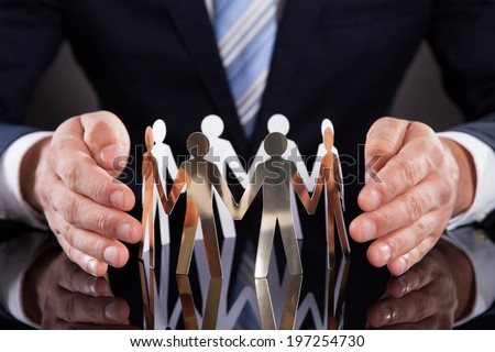 Midsection of businessman's hands protecting team of paper people on desk against black background - stock photo