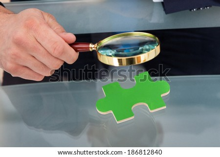Midsection of businessman scrutinizing green puzzle piece with magnifying glass at desk - stock photo