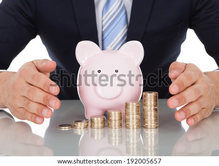 Midsection of businessman sheltering coins and piggybank at desk