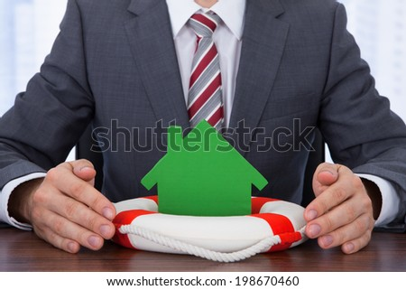 Midsection of businessman sheltering house with lifebuoy at desk - stock photo