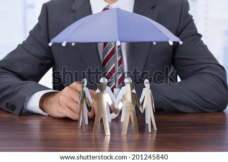 Midsection of businessman sheltering paper people with umbrella at desk - stock photo