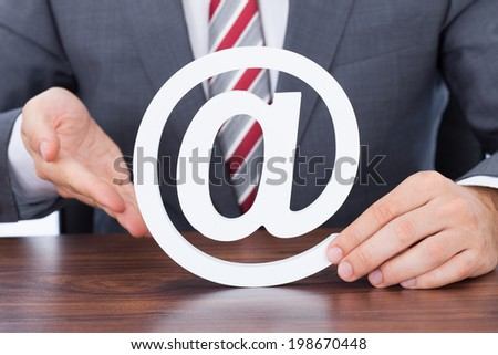 Midsection of businessman shielding internet icon at desk - stock photo