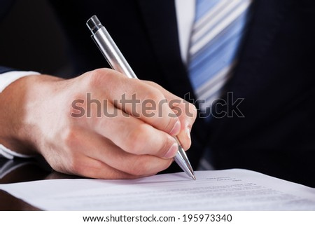 Midsection of businessman signing contract paper at desk - stock photo