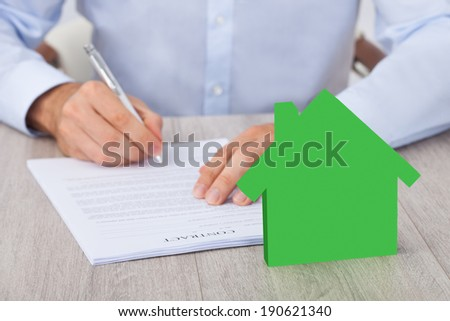 Midsection of businessman signing contract with green model home at desk - stock photo