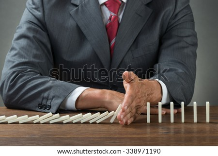 Midsection of businessman stopping dominoes falling on wooden desk - stock photo