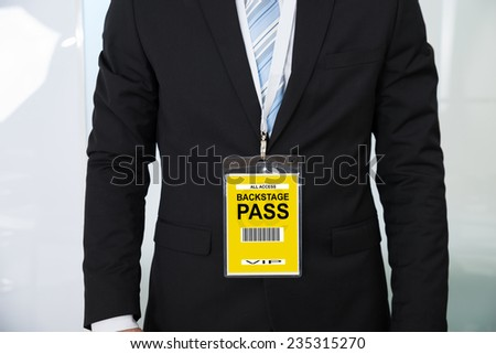 Midsection of businessman wearing backstage pass in office - stock photo