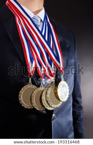 Midsection of businessman wearing gold medals against black background - stock photo