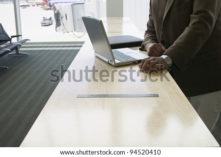 Midsection of businessman with laptop - stock photo