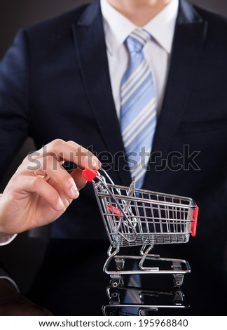 Midsection of businessman with shopping cart model at desk