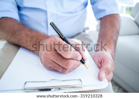 Midsection of businessman writing on notepad