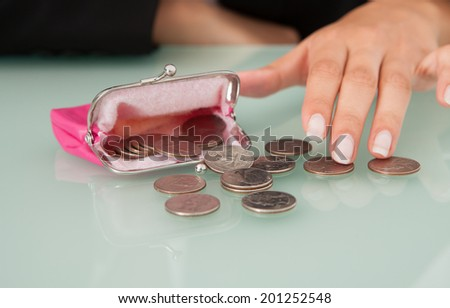 Midsection of businesswoman counting coins spilled from pink purse at office desk - stock photo