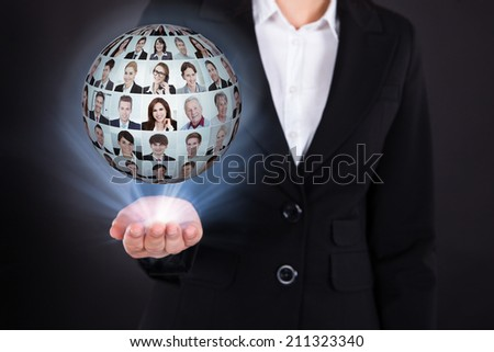 Midsection of businesswoman holding businesspeople collage in sphere over black background - stock photo