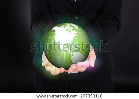 Midsection of businesswoman holding glowing green globe representing ecofriendly environment.