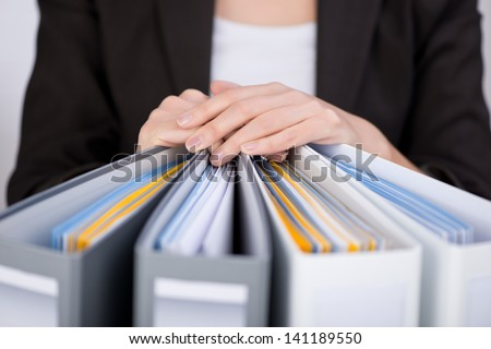 Midsection of businesswoman with binders at office - stock photo