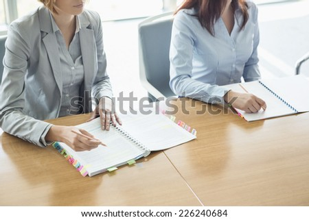 Midsection of businesswomen with books at table in office - stock photo