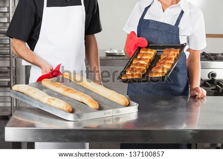 Midsection of chefs holding trays of baked breads in commercial kitchen