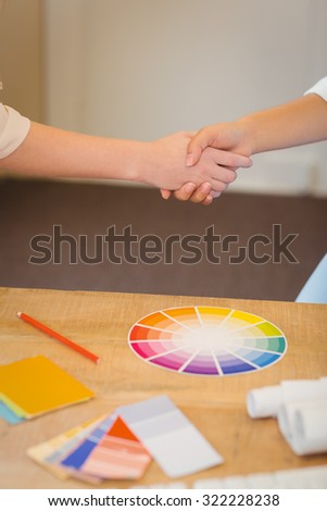 Midsection of clients shaking hands with businesswoman over color samples on table in office