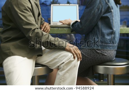 Midsection of couple with laptop at restaurant - stock photo