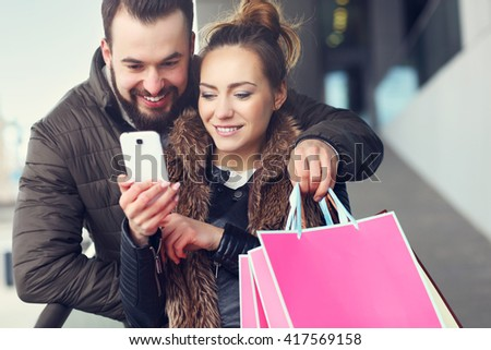 Midsection of couple with shopping bags and smartphone in city - stock photo
