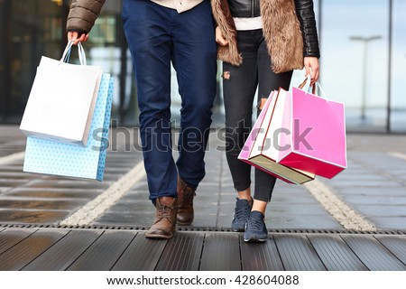 Midsection of couple with shopping bags in city - stock photo