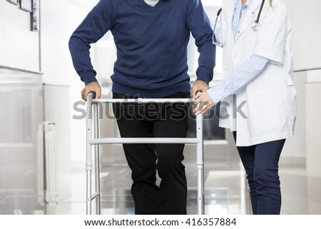 Midsection Of Doctor Assisting Senior Man With Walker - stock photo