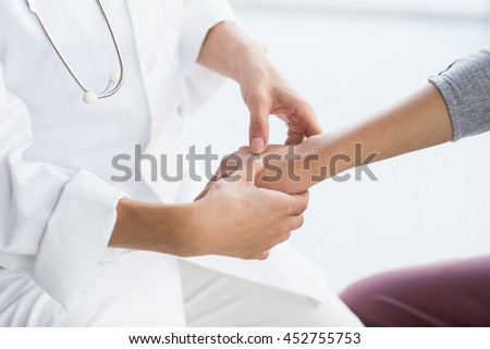 Midsection of doctor examining female patient at clinic