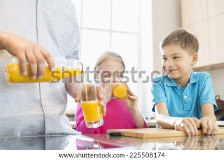 Midsection of father serving orange juice for children in kitchen - stock photo