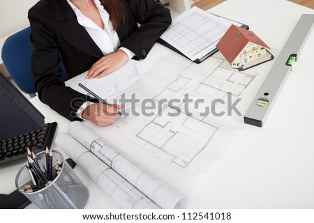 Midsection of female architect with model house, blueprints and spirit level on office desk - stock photo