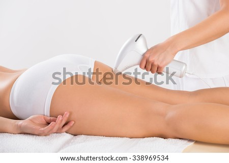 Midsection of female beautician using laser machine on young customer's leg at salon - stock photo