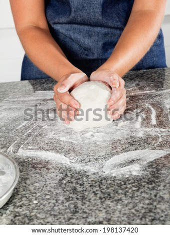 Midsection of female chef kneading dough on commercial kitchen counter - stock photo