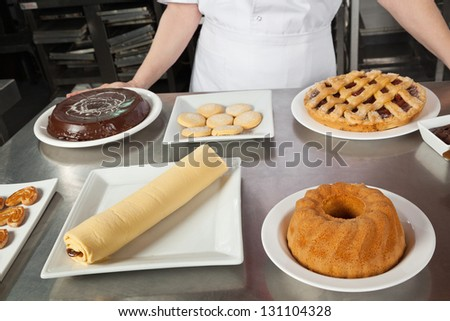 Midsection of female chef with variety of sweet dishes on commercial kitchen counter - stock photo