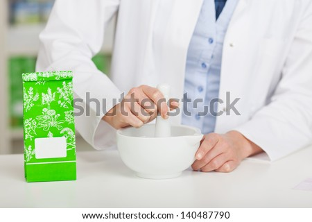 Midsection of female pharmacist grinding medicine at pharmacy counter - stock photo