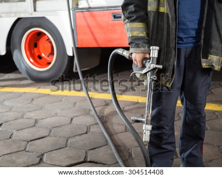 Midsection of firefighter holding water hose while standing at fire station - stock photo