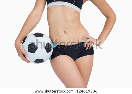 Midsection of fit woman in sportswear with football standing over white background