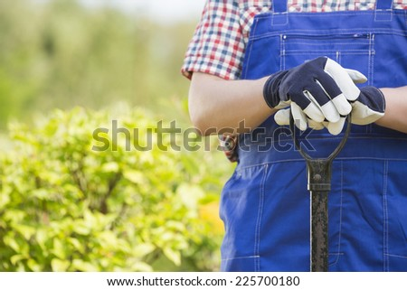 Midsection of gardener holding spade in plant nursery - stock photo