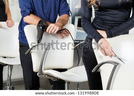 Midsection of hairdressers with dryer and scissors standing behind chairs in salon - stock photo