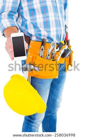 Midsection of handyman showing smartphone on white background - stock photo