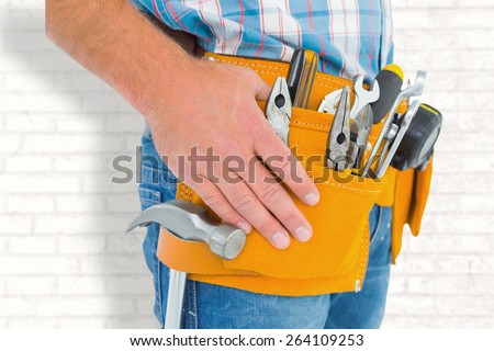 Midsection of handyman wearing tool belt against white wall