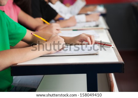 Midsection of high school students writing on paper at desk in classroom - stock photo