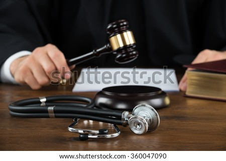 Midsection of judge striking mallet with stethoscope at desk in courtroom - stock photo