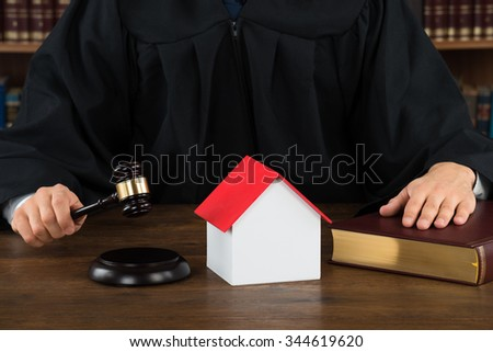 Midsection of judge with house model hitting gavel at desk in courtroom - stock photo