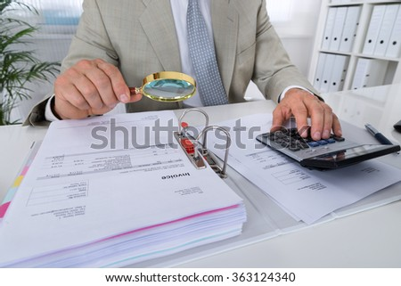 Midsection of male accountant using calculator while holding magnifying glass to analyze bills in office - stock photo