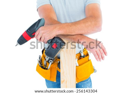 Midsection of male carpenter with power drill and plank on white background