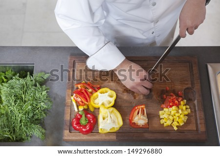 Midsection of male chef dicing red and yellow bell peppers in commercial kitchen - stock photo