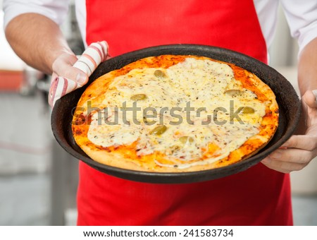 Midsection of male chef holding delicious pizza in pan at commercial kitchen - stock photo