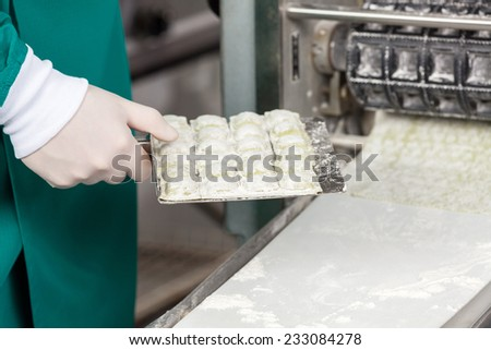 Midsection of male chef holding ravioli pasta tray by automated machine at commercial kitchen - stock photo