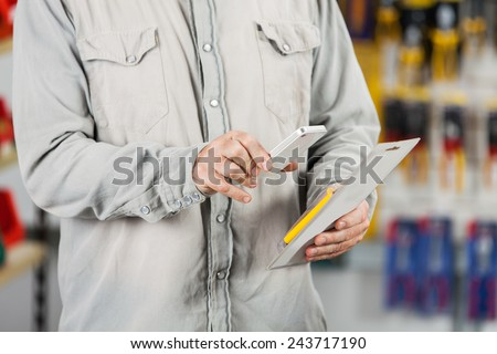 Midsection of male customer scanning tool packet through mobilephone in hardware store - stock photo