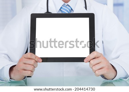Midsection of male doctor displaying digital tablet at desk in hospital - stock photo