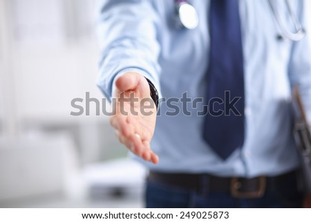 Midsection of male doctor extending his hand for a handshake in clinic