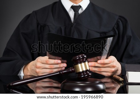Midsection of male judge holding file with mallet on desk against black background - stock photo